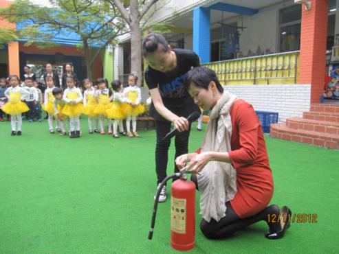 小何现场教幼儿园老师怎样正确操作灭火器。